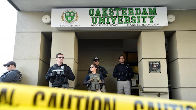 U.S. marshals stand at the entrance of Oaksterdam University in Oakland, Calif., on Monday, April 2, 2012. The federal agents raided the medical marijuana training school at the heart of California's pot legalization movement. (AP Photo/Noah Berger)