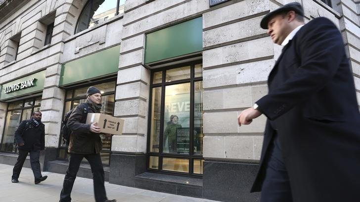Pedestrians walk past a branch of Lloyds bank in central London