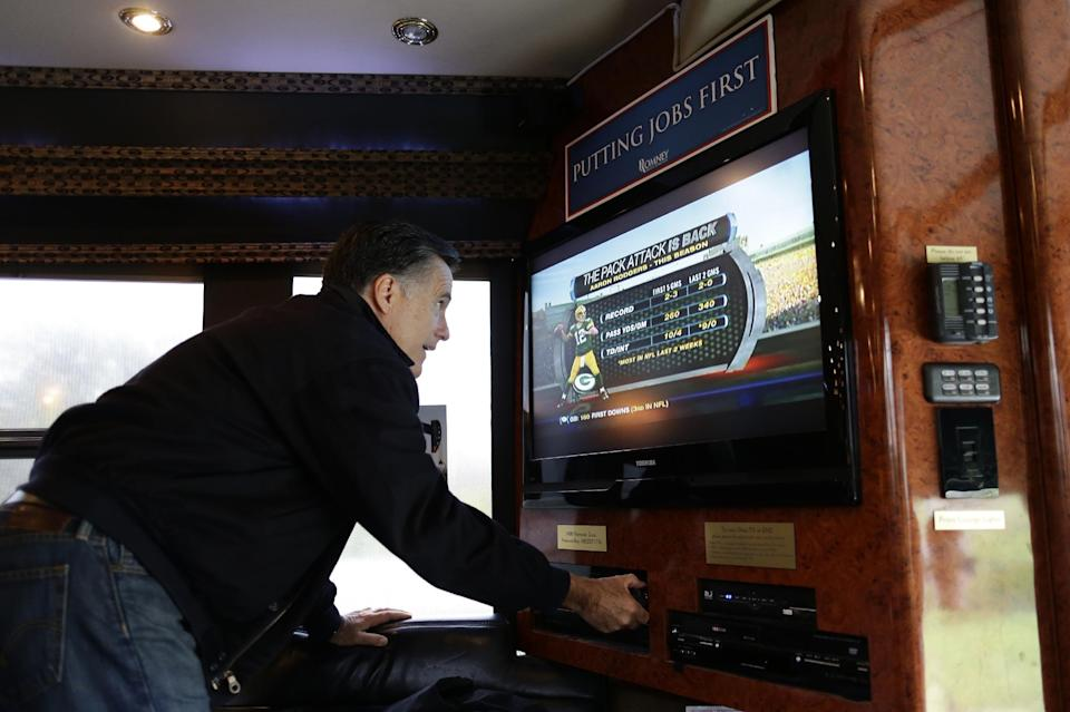 Republican presidential candidate and former Massachusetts Gov. Mitt Romney tunes in the Green Bay Packers football game on his campaign bus en route to Celina, Ohio, for a campaign rally, Sunday, Oct. 28, 2012. (AP Photo/Charles Dharapak)