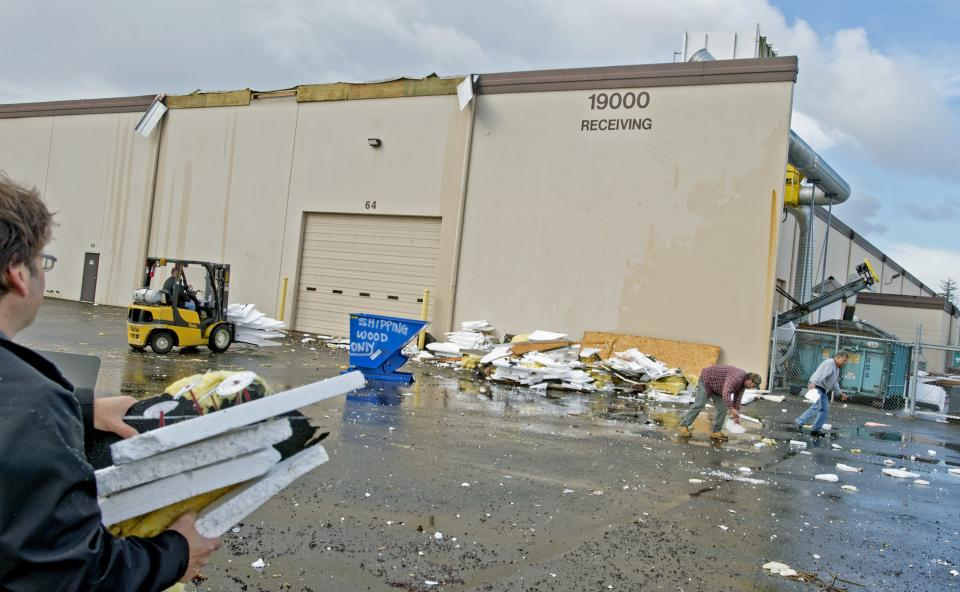 Workers clean up debris at Northwest Door after a funnel cloud hit several locations in Fredrickson, Wash., near Tacoma Monday, Sept. 30, 2013. The roof was damaged, planted trees broken and many styrofoam sheets which had been stored outside were blown about. (AP photo/ The News Tribune, Peter Haley) SEATTLE BROADCAST OUT
