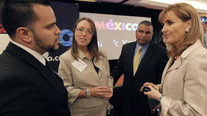 Mexico Secretary of Tourism Gloria Guevara Manzo, right, speaks with Mario Robles of AeroMexico, left, and Christina Scott of Sabre, center, during the MEX Day event on Monday, July 16, 2012 in Dallas, Texas. (Brandon Wade /AP Images for Mexico Tourism)