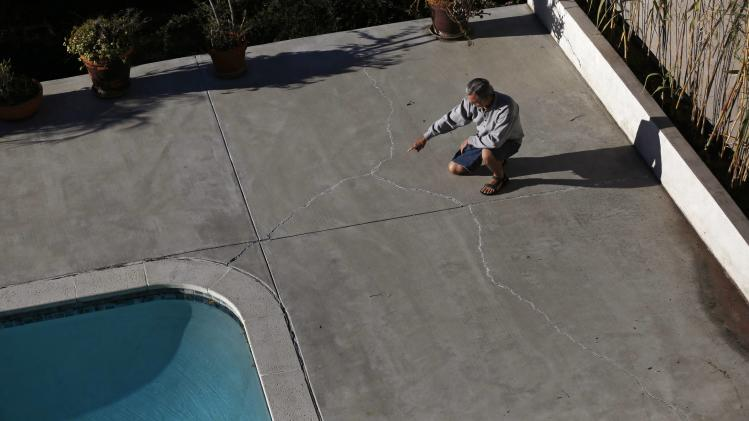 Homeowner Gary Gless points at cracks in cement in his backyard in Los Angeles