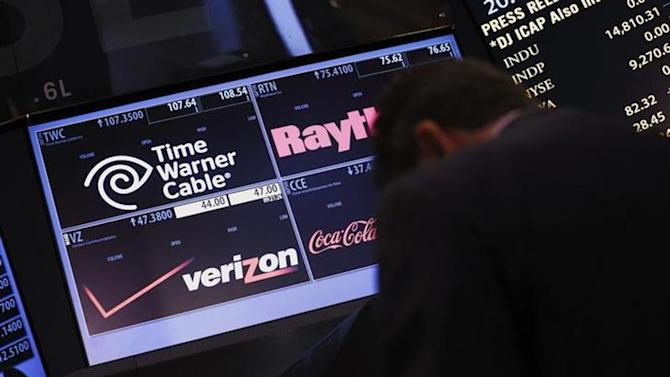 A trader passes by the post that trades Verizon wireless and Time Warner Cable on the floor of the New York Stock Exchange September 3, 2013.