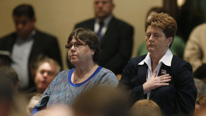 Angela Richerson, left, of McCloud, Okla., who lost her mother, Norma Jean Johnson, in the Oklahoma City bombing, and Rebecca J. Allen, right, Chief of Staff of the Department of Defense, Defense Security Service, stand during the reading of the names of the bombing victims during a ceremony to mark the 18th anniversary, in Oklahoma City, Friday, April 19, 2013. (AP Photo/Sue Ogrocki)