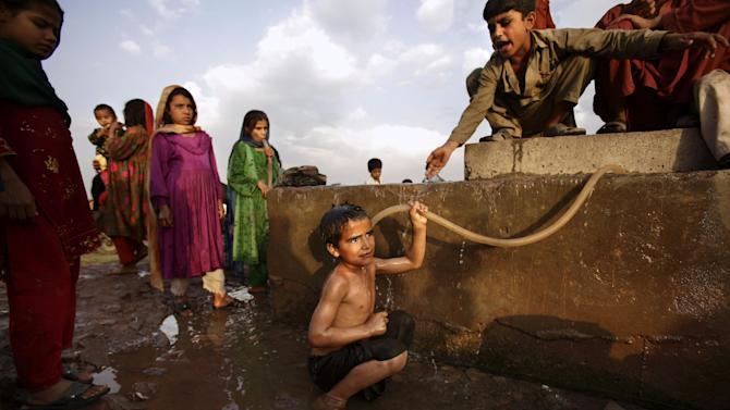 In this Tuesday, May 15, 2012, photo, Afghan refugee boy, Doost Hamid, 7, bottom center, bathes at a water point in a slum area on the outskirts of Islamabad, Pakistan.  Hundreds of thousands of Afghan refugees are in limbo as Pakistan, increasingly frustrated with hosting the world's largest and longest-running refugee population, weighs whether to renew their refugee status by the end of this year. A large-scale return of the 1.7 million Afghan refugees currently living in Pakistan would be a massive problem for Afghanistan at a time when it's already struggling to maintain security in the face of an American troop withdrawal. But Pakistan increasingly seems to be angry at a refugee population that many feel has overstayed its welcome. (AP Photo/Muhammed Muheisen)