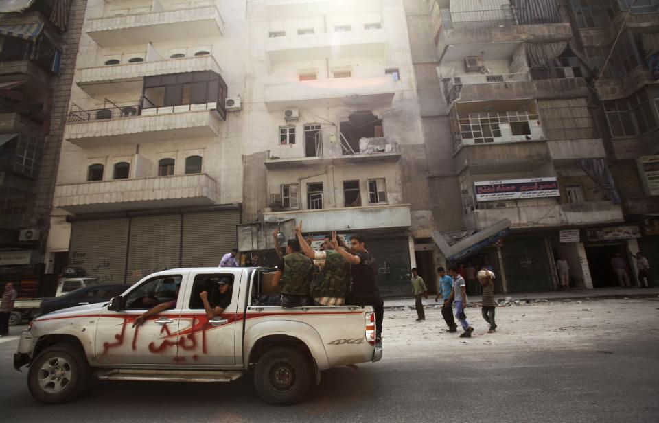 "Syrian rebel fighters flash the victory sign while moving past a building destroyed by government shelling in Aleppo, Syria, Tuesday, Sept. 11, 2012. The graffiti on the truck reads, ""free army."" (AP Photo/Muhammed Muheisen)"