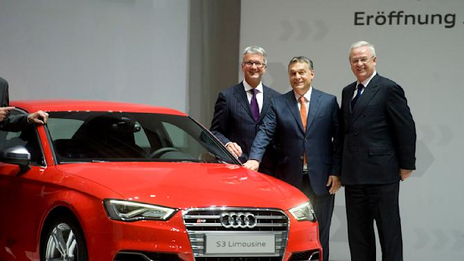 From left, Chairman of Audi AG Rupert Stadler, Hungarian Prime Minister Viktor Orban and Chairman of Volkswagen AG Martin Winterkorn stand necxt to the sports version of Audi A3 Limousine during the ceremonial inauguration Audi's new car manufacturing plant in Gyor, 124 kms west of Budapest, Hungary, Wednesday, June 12, 2013. (AP Photo/MTI, Szilard Koszticsak)