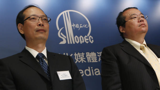Sinopec representatives, News Spokesperson Lu Dapeng, and Vice President of Sinopec Chemical Commercial Holdings Company Ltd. Zhang Guoming attend a press conference in Hong Kong Thursday Aug. 9, 2012. Chinese oil company Sinopec, Thursday, is promising to clean up millions of its tiny plastic pellets that washed up on beaches across Hong Kong after they fell off a ship during a strong typhoon. (AP Photo/Kin Cheung)