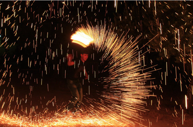 A Palestinian boy plays with fireworks as he celebrates the start of the  Muslim holy month of Ramadan in the West Bank city of Nablus, Thursday, July 19, 2012.  (AP Photo/Nasser Ishtayeh)