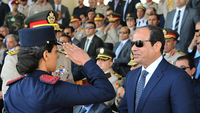 This image released by Egypt's official Middle East News Agency (MENA) shows President Abdel-Fattah el-Sissi as he is saluted by a female cadet at a military graduation in Cairo, Tuesday, June 24, 2014. President el-Sissi said Tuesday he will not interfere in court rulings, rebuffing calls from the United States and other Western governments that he pardon or commute the sentences of three Al-Jazeera journalists handed heavy prison terms a day earlier.(AP Photo/MENA)