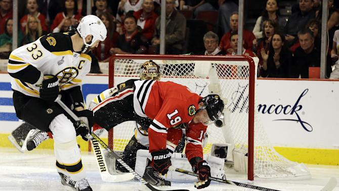 Boston Bruins defenseman Zdeno Chara (33) controls the puck against Chicago Blackhawks center Jonathan Toews (19) during the second period of Game 1 in their NHL Stanley Cup Final hockey series on Wednesday, June 12, 2013, in Chicago. (AP Photo/Nam Y. Huh)