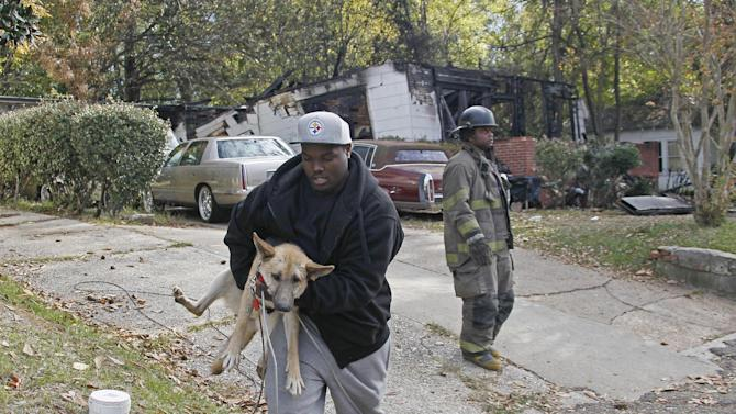 A resident of this west Jackson, Miss., home removes one of several dogs, Wednesday, Nov. 14, 2012, that were at the back of a house that local authorities said a small plane carrying three people crashed into Tuesday evening. Federal investigators are working with Jackson, Miss., Fire Department investigators to inspect the home and aircraft. The home's resident  escaped with non-life threatening injuries but authorities confirmed the plane's passengers were dead.  (AP Photo/Rogelio V. Solis)