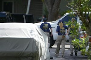 FBI personnel walk through the complex surrounding …