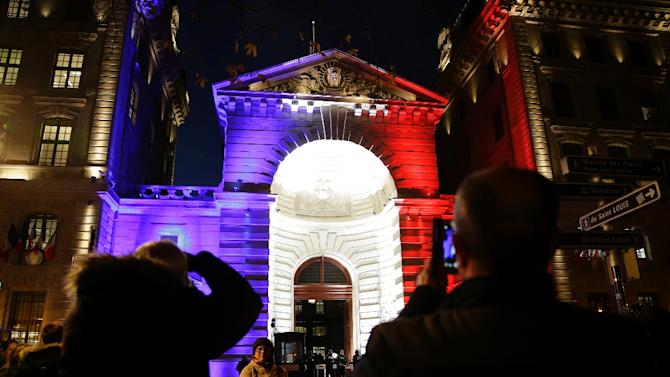 People takes photos on November 26, 2015 of the Paris police headquarters illuminated with the French national colours in tribute to the victims of the November 13 attacks in the capital