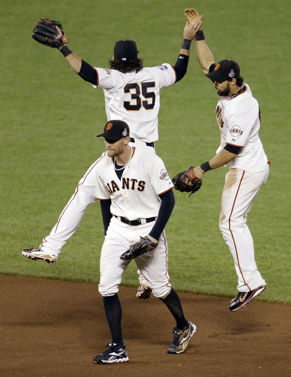 San Francisco Giants' Angel Pagan leaps up to celebrate with Brandon Crawford and Hunter Penc after the Giants beat the Detroit Tigers 2-0 in Game 2 of baseball's World Series Thursday, Oct. 25, 2012, in San Francisco. (AP Photo/Eric Risberg)