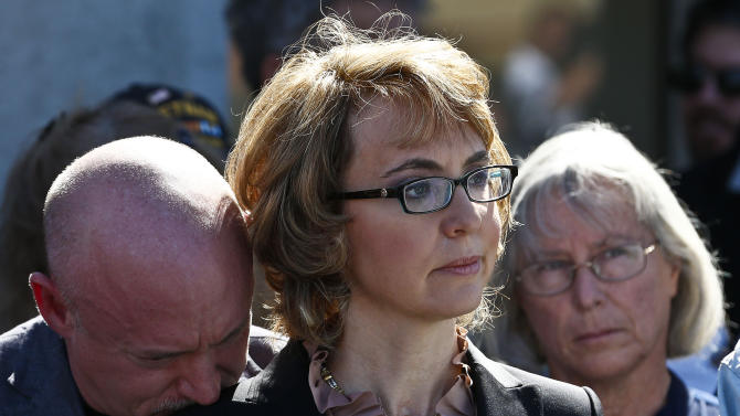 Former Rep. Gabrielle Giffords, center, is joined by her husband Mark Kelly, left, and Emily Nottingham, mother of shooting victim Gabe Zimmerman, listening to a speaker as they returned to the site of a shooting that left her critically wounded to urge key senators to support expanded background checks for gun purchases, Wednesday, March 6, 2013, in Tucson, Ariz. (AP Photo/Ross D. Franklin)