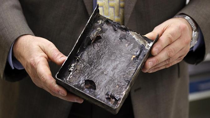 """National Transportation Safety Board's Joseph Kolly, holds an fire-damaged battery casing from the Japan Airlines Boeing 787 Dreamliner that caught fire at Logan International Airport in Boston, at the NTSB laboratory in Washington, Thursday, Jan. 24, 2013. The battery that caught fire in Boston shows evidence of short-circuiting and a chemical reaction known as """"thermal runaway,"""" in which an increase in temperature causes progressively hotter temperatures, federal accident investigators said. However, it's not clear to investigators which came first, the short-circuiting or the thermal runaway. (AP Photo/Manuel Balce Ceneta)"""
