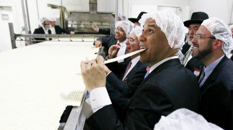 Newark Mayor Cory Booker eats a piece of a large matzo that was baked during the grand opening of the headquarters for the Manischewitz company, Tuesday, June 14, 2011 in Newark, N.J. The kosher product company claims the matzo is the world's largest. (AP Photo/Julio Cortez)