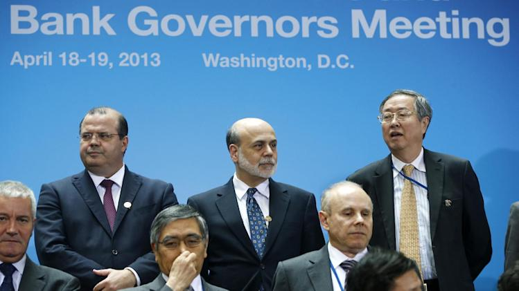 Federal Reserve Chairman Ben Bernanke, center, stands with China Central Bank Gov. Zhou Xiaochuan, right, and Brazil Central Bank Gov. Alexandre Tombini during a group photo of the G20 finance ministers and central bank governors on the sidelines of their meeting at World Bank Group International Monetary Fund Spring Meetings in Washington, Friday, April 19, 2013. (AP Photo/Charles Dharapak)