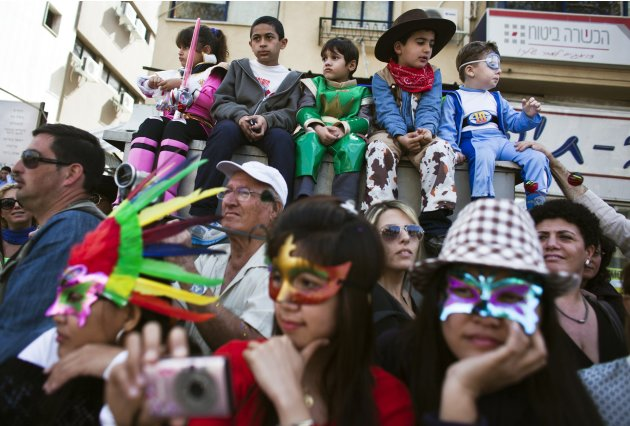 People, some dressed in costumes, watch the annual parade for the Jewish holiday of Purim, near Tel Aviv