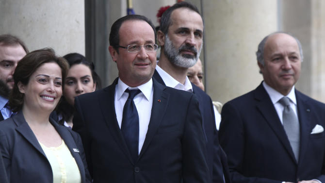 French President Francois Hollande, second from left, head of the new Syrian National Coalition for Opposition and Revolutionary Forces Mouaz al-Khatib, second from right, Syrian opposition member Suheir Atassi, left, and French Foreign Minister Laurent Fabius, right, pose for photos, prior to a meeting, at the Elysee Palace, in Paris, Saturday, Nov. 17, 2012. France has taken a leading role among Western countries in supporting Syria's rebels. On Tuesday, it became the first Western nation to formally recognize Syria's newly formed opposition coalition as the sole legitimate representative of the Syrian people. (AP Photo/Thibault Camus)