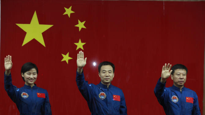 Chinese astronauts from left., Liu Yang, Jing Haipeng and Liu Wang wave from behind a glass enclosure as they meet the press at the Jiuquan satellite launch center near Jiuquan in western China's Gansu province, Friday, June 15, 2012. China will send its first woman into space Saturday along with two other astronauts to work on a temporary space station for about a week, in a key step toward becoming the only third nation to set up a permanent base in orbit. (AP Photo/Ng Han Guan)
