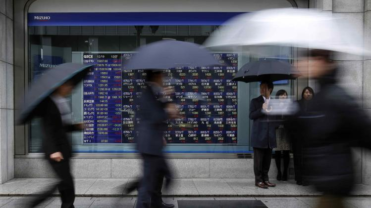 Pedestrians holding an umbrella walk past an electronic board displaying stock prices outside a brokerage in Tokyo