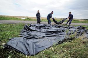 Ukrainian rescue workers collect bodies of victims …