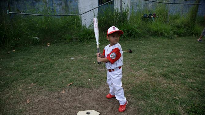 In this Oct. 25, 2012 photo, a young player holds his bat during training at a baseball school in Maracay, Venezuela.  Many of the boys are inspired by the example of Detroit Tigers slugger Miguel Cabrera, who learned the game on this very field. Their baseball school in the poor neighborhood where Cabrera grew up is one of many across Venezuela, a web for training young ballplayers that has made the country a powerhouse in the U.S. major leagues. (AP Photo/Ariana Cubillos)