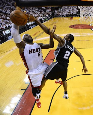 Kawhi Leonard defends a LeBron James drive. (AP)