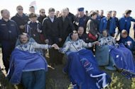 Astronauts Tom Marshburn (R), Chris Hadfield (L) and Roman Romanenko (C) join hands after landing aboard the Russian Soyuz space capsule in Kazakhstan on May 14, 2013. The landing marks the end of a half-year mission to the International Space Station that saw Hadfield shoot to global stardom through his Twitter microblog