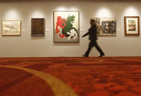 A visitor walks past a painting of Tyeb Mehta's Mahisasura during a preview of Christie's first art auction in India