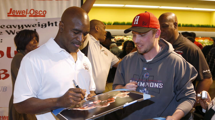 Five-time heavyweight boxing champion Evander Holyfield signs autographs during a promotional stop for Holyfield's barbecue sauce at a Chicago grocery store Saturday, Feb. 16, 2013. (AP Photo/Charlie Arbogast)