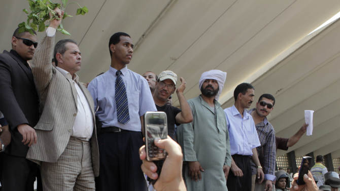 """In this Tuesday Aug. 7, 2012 photo, Tawfiq Okasha holding some plants, 2nd left, rallies his supporters against Egyptian President Mohammed Morsi and the Muslim Brotherhood at the funeral of 16 Egyptian soldiers killed in the Egyptian border town of Rafah on Aug 5, 2012. He emerged as one of the most popular television personalities of post-revolution Egypt by railing against the revolution, a bombastic conservative who every night mocked the country's """"enemies"""" --everyone from leftists and Islamists to Freemasons and Zionists-- with rants full of abuse and earthy humor. Now Tawfiq Okasha presents himself as the country's champion against a takeover by the Muslim Brotherhood, calling protests that took place Friday. (AP Photo/Thomas Hartwell)"""