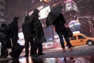 Pedestrians walk through Times Square as it snows Wednesday, Nov. 7, 2012, in New York. Coastal residents of New York and New Jersey faced new warnings to evacuate their homes and airlines canceled hundreds of flights as a new storm arrived Wednesday, only a week after Superstorm Sandy left dozens dead and millions without power. (AP Photo/Frank Franklin II)