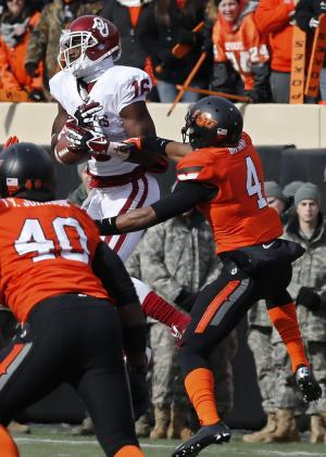 Oklahoma State cornerback Justin Gilbert (4) breaks up a pass intended for Oklahoma wide receiver Jaz Reynolds (16) in the first quarter of an NCAA college football game in Stillwater, Okla., Saturday, Dec. 7, 2013. (AP Photo/Sue Ogrocki)