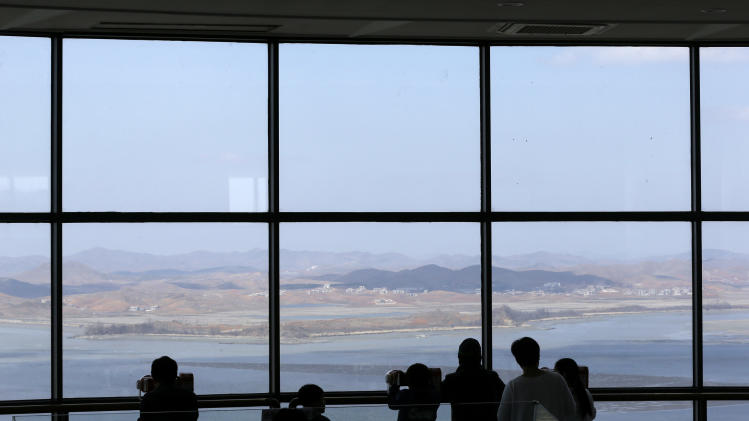 Visitors watch North Korean territory through binoculars at the unification observation post near the border village of Panmunjom, that has separated the two Koreas since the Korean War, in Paju, north of Seoul, South Korea, Sunday, April 7, 2013. South Korea said its top military officer has put off a plan to visit Washington due to current tension with North Korea. (AP Photo/Lee Jin-man)