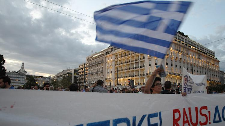 "A protestor waves a Greek flag in Athens on Monday, Oct. 8, 2012 during an union anti-austerity rally a day before the visit by German Chancellor Angela Merkel. The authorities are keen to prevent embarrassing riots. More than 7,000 police will be on security duty in the capital from early Tuesday, while public gatherings will be banned in much of the city center and on a 100-meter (yard) radius from the route her motorcade will follow. The ban will not affect the main protests, but will prevent demonstrators from reaching the German embassy, where a populist right wing party was planning a protest. Banner says ""Merkel leave""(AP Photo/Thanassis Stavrakis)"