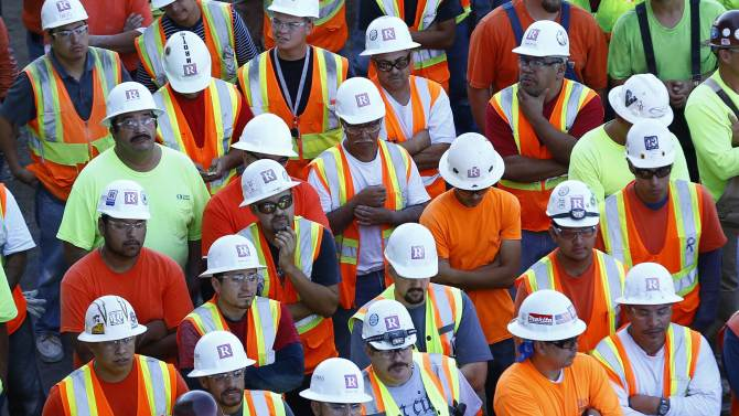 Construction workers wait to put on pink hard hats  to promote the start of  Breast Cancer Awareness Month in La Jolla