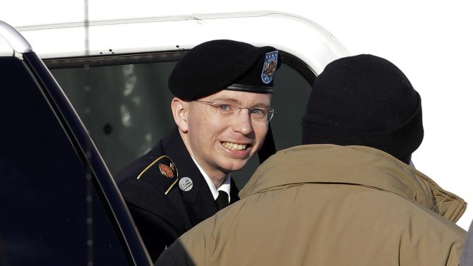 FILE - In this Nov. 28, 2012 file photo, Army Pfc. Bradley Manning, center, steps out of a security vehicle as he is escorted into a courthouse in Fort Meade, Md., for a pretrial hearing. Visual journalists from many organizations have experienced difficulty capturing an unobstructed view of Manning entering and exiting a courthouse on the U.S. Army Post Fort Meade because of the often heavy security presence around him. This particular image was the rare exception to the daily coverage, as Manning smiled while looking toward the cameras, unobstructed by security. (AP Photo/Patrick Semansky, File)