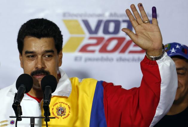 Venezuela's President Nicolas Maduro shows his ink-stained finger after voting during municipal elections in Caracas
