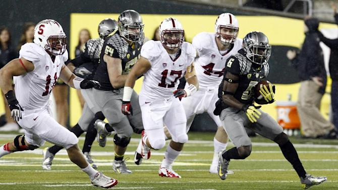 Oregon running back De'Anthony Thomas, right, breaks into the open field ahead of Stanford defenders, from left,Shayne Skov, A. J. Tarpley and Chase Thomas  during the first half of their NCAA college football game in Eugene, Ore., Saturday, Nov. 17, 2012.(AP Photo/Don Ryan)
