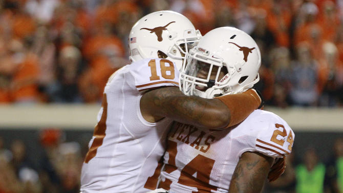 Texas right end D.J. Grant (18) and running back Joe Bergeron (24) celebrate Bergeron's touchdown against Oklahoma State in the fourth quarter of an NCAA college football game in Stillwater, Okla., Saturday, Sept. 29, 2012. Texas won 41-36. (AP Photo/Sue Ogrocki)