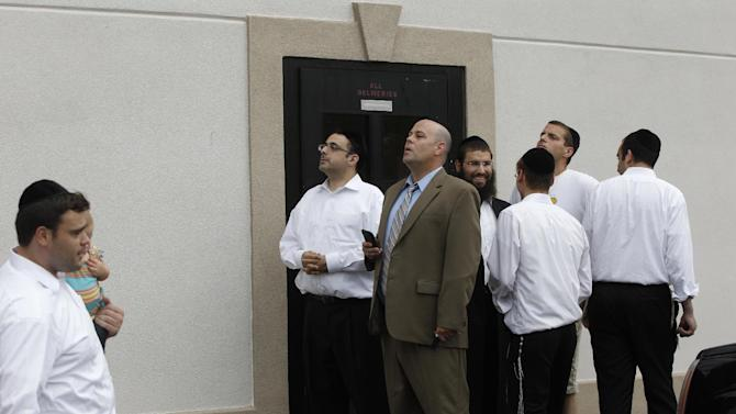 Members of a  Jewish wedding party watch as the motorcade of Republican presidential candidate and former Massachusetts Gov. Mitt Romney drives past for a campaign fundraising event in Lakewood, N.J., Wednesday, Aug. 8, 2012. Romney's motorcade rolled into the fundraiser as a bride and groom were posing for pictures in the parking lot outside the hall in Lakewood. Several guests in yarmulkes who were standing around turned their cameras away from the couple, and a few chased the motorcade around the corner.(AP Photo/Charles Dharapak)