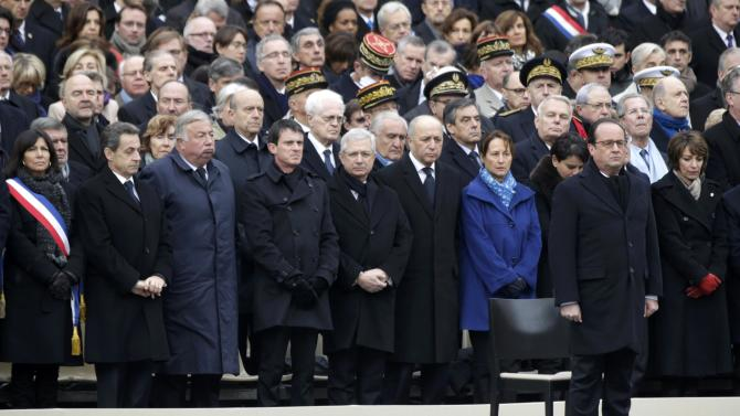French President Francois Hollande stands in front of members of French government and French officilas during a ceremony to pay a national homage to the victims of the Paris attacks at Les Invalides monument in Paris