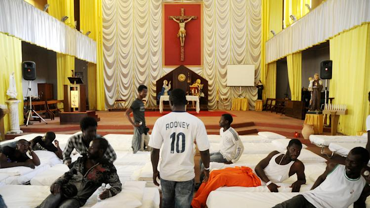 In this picture taken Sunday, June 15, 2014, migrants from Africa are temporarily sheltered in the Catholic church of St. Curato D'Ars in Palermo, Sicily, Italy. The Italian coast guard and navy have rescued more than 300 migrants whose boats ran into trouble in the Mediterranean Sea and recovered the bodies of 10 migrants whose dinghy had overturned, Sunday. Naval official Salvatore Scimone said 39 survivors on Saturday night had grabbed onto the dinghy until rescuers plucked them to safety aboard another boat. He said he feared that an undetermined number of others were missing in the sea north of Libya. In a separate rescue, three Italian ships took aboard 281 migrants who said they were Syrian and whose fishing boat ran into problems. (AP Photo/Alessandro Fucarini)