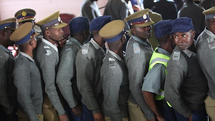 Zimbabwean police officers wait in a queue to cast their votes, at a polling station in Harare, Monday, July, 15, 2013. Officials of Zimbabwe's election commission said Sunday early voting started for police and security personnel who will be on duty during the nation's crucial elections on July 31. (AP Photo/Tsvangirayi Mukwazhi)