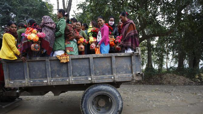 People arrive on a vehicle to take part in a parade marking an Elephant Festival event at Sauraha in Chitwan