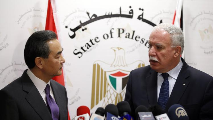 Chinese Foreign Minister Wang Yi listens to his Palestinian counterpart Malki as they delivery joint statements in Ramallah