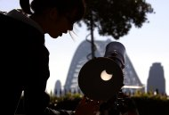 A woman adjusts a telescope showing on a screen the annular solar eclipse from atop Observatory Hill in Sydney May 10, 2013.   REUTERS/David Gray     (AUSTRALIA - Tags: ENVIRONMENT)